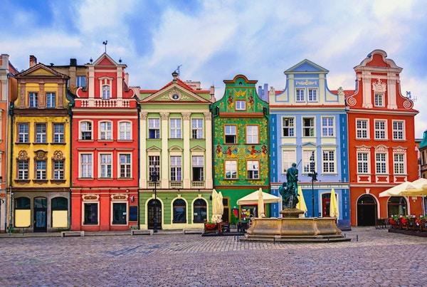 Torg med brostensbelagt gate, fontene og fargerike hus