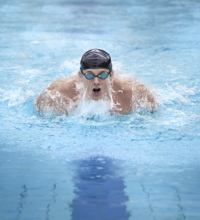 Svømmer i hette, puster og svømmer i butterfly-teknikk