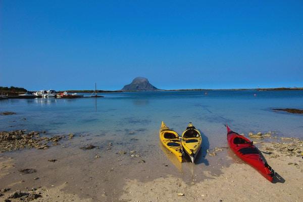 Tre kajakker, to gule og en rød som ligger ved stranda med båter i bakgrunnen