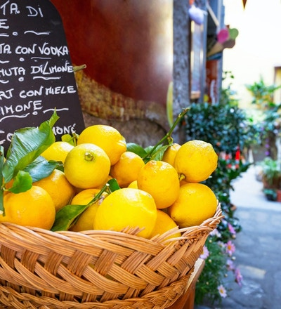 Flettet kurv full av sitroner på den italienske gaten od Corniglia