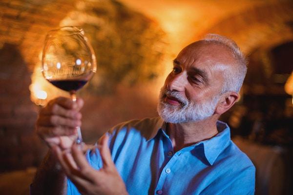 Familieferie i Langhe-regionen, Piemonte, Italia: En mann velger og smaker vin