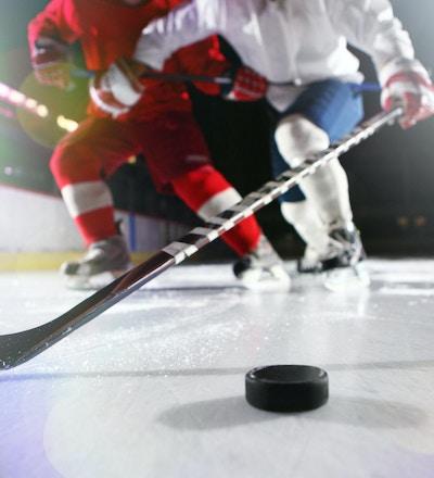 Isnivåbilde av mannlige ishockeyspillere i en takling under et spill. De høye hvite sokkene og de mørkeblå buksene til hockeyspilleren kan sees. Det er en hockeyspinne som strekker seg etter pucken. En hockeyspuck som kaster to skygger er på isen i høyre hjørne av bildet.