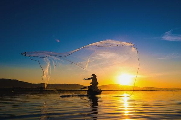 Fisker i aksjon under fiske om morgenen, Vietnam.
