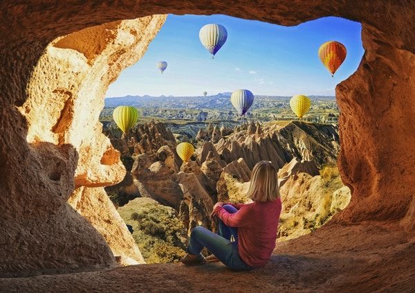 Kvinne som ser på fargerike luftballonger som flyr over dalen ved Cappadocia, Tyrkia. Vulkanske fjell i Goreme nasjonalpark.