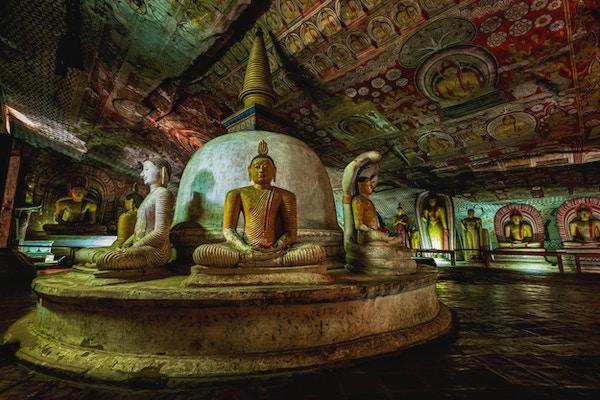 Buddha-statue inne i Dambulla-huletempelet, Sri Lanka. Dambulla grottetempel, også kjent som Golden Temple of Dambulla, er et verdensarvsted på Sri Lanka, som ligger i den sentrale delen av landet. Dette stedet ligger 148 km øst for Colombo og 72 km nord for Kandy. Det er det største og best bevarte huletempelkomplekset på Sri Lanka. Dette tempelkomplekset dateres tilbake til det første århundre f.Kr. Det er mer enn 80 dokumenterte grotter i området rundt. De viktigste attraksjonene er spredt over 5 huler, som inneholder statuer og malerier. Disse maleriene og statuene er relatert til Lord Buddha og hans liv. Det er totalt 153 Buddha-statuer, 3 statuer av srilankanske konger og 4 statuer av guder og gudinner.