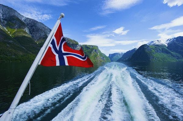 Norsk flagg på baksiden av en ferge som krysser fjordene