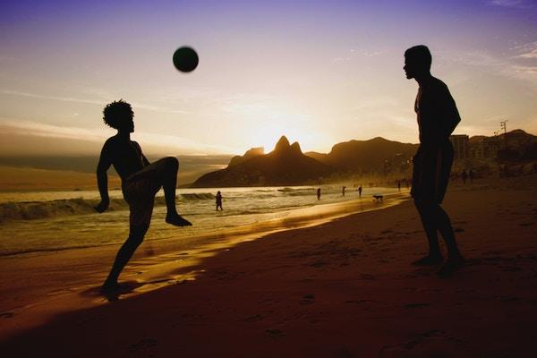 To menn som spiller fotball på en strand i Rio de Janeiro i solnedgangen.