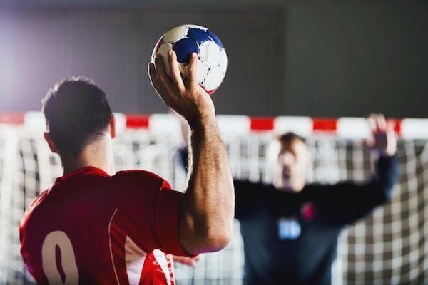 Straffespark. Sett bakfra av håndballspiller som skyter i mål, mens keeper er i bakgrunnen med hendene løftet.