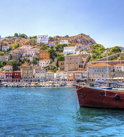 Utsikt over den vakre greske øya Hydra. Det er en fiskebåt i forgrunnen og litt lokal arkitektur i bakgrunnen. Utsikten er fra sjøen da cruiseskipet ankom i Hydra.