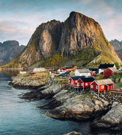 Norsk fiskevær på Lofoten-øyene i Norge. Dramatiske solnedgangskyer som beveger seg over bratte fjelltopper