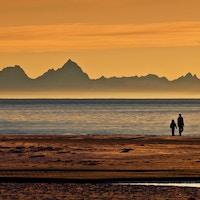To mennesker i silhuett på stranda med fantastisk midnattssol med fjell i bakgrunnen.