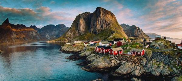 Norsk fiskevær ved Lofoten i Norge. Dramatiske solnedgangsskyer som beveger seg over bratte fjelltopper