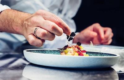 Kokk pynter maten før servering.