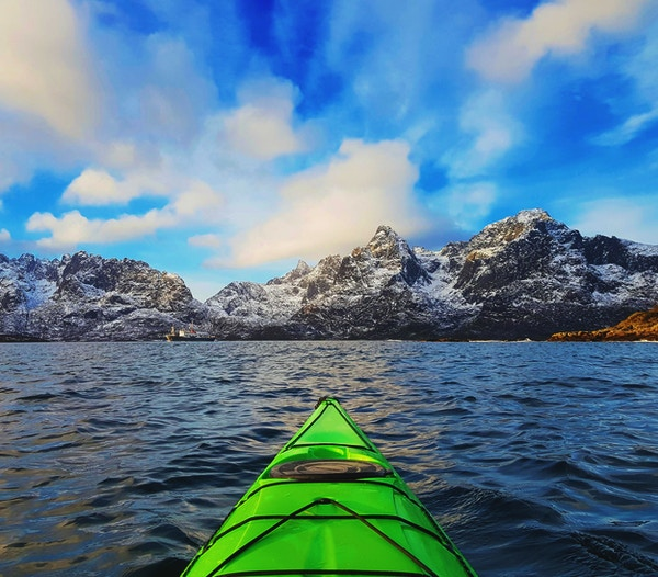 Liten grønn kajakk i fjorden i Lofoten, omgitt av snødekte fjell og blå himmel. Norge.