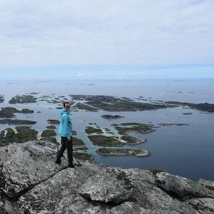 Kvinne på fjelltopp med fantastisk utsikt over hav og øyer.