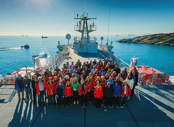 En gruppe reisende smiler mot kamera ombord på en stor båt som ligger i havnen