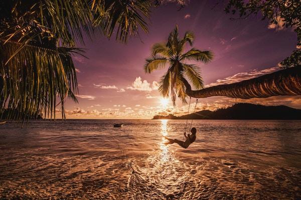 Ung, glad kvinne som gleder seg i en vakker solnedgang på stranden mens hun svinger over vannet.