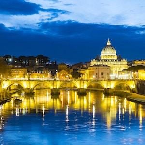 Vakkert opplyst elveutsikt over Ponte Sant'Angelo og Vatikanstaten Peterskirken i skumringen i Roma, Italia om vinteren