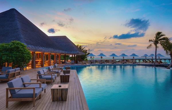 Stort svømmebasseng med solstoler rundt, havet i bakgrunnen i kveldslys.