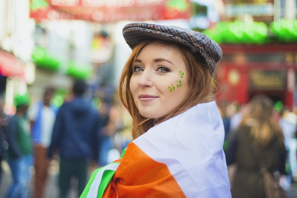 Smilende rødhåret irsk jente med ansiktsmalt og det irske flagget og tweedhetten i Temple Bar, Dublin, Irland