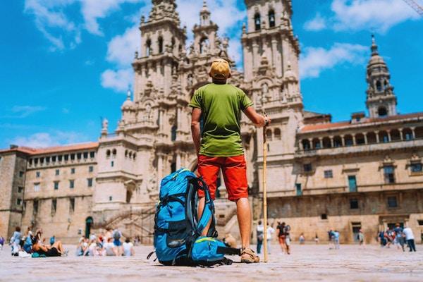 Ung backpacker-pilegrim som står på Obradeiro-plassen (torget) - hovedtorget i Santiago de Compostela.