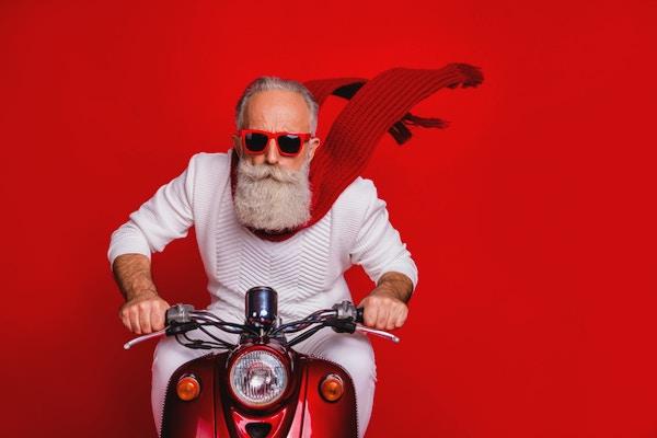 Nærbilde av kul pensjonist som sykler med luftvind som blåser iført hvit genser som er isolert over rød bakgrunn