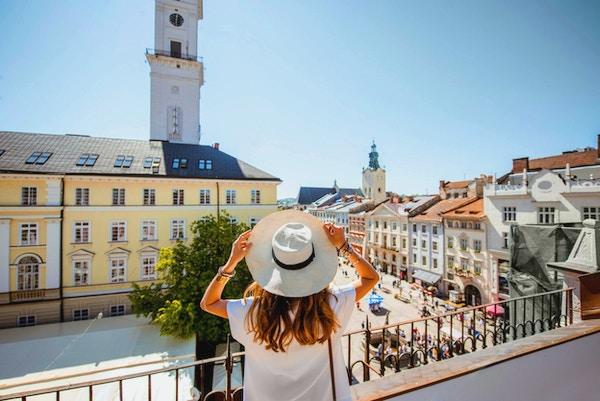 Ung kvinnelig turist som nyter en flott utsikt over den gamle bydelen med rådhustårnet i Lviv sentrum i det solfylte været i Ukraina