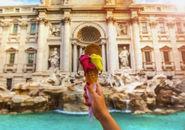Hånd som holder fargerik gelato foran den berømte ikoniske Trevifontenen i Roma, Italia.
