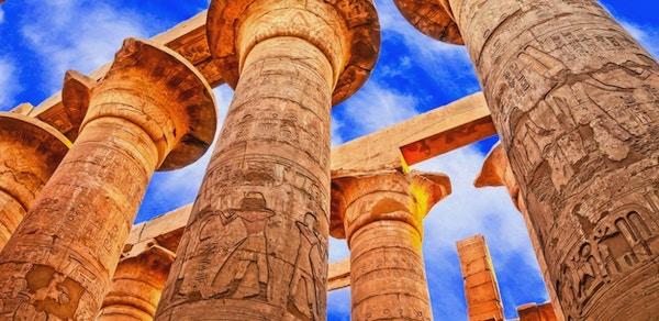 Egyptiske søyker med hieroglyfer fotografert nedenfra mot en blå himmel.