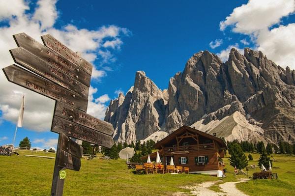 Samling med veiskilt i forgrunnen, fjellhytte og karakterisktiske fjellformasjoner fra Dolomittene i bakgrunnen.