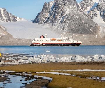 Hurtigruten  i en fjord med fjell i bakgrunnen og en person i forgrunnen.