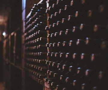 En mørk vinkjeller med hundrevis av vinflasker stablet i en vegghylle