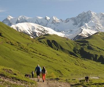 Turgåere i fjellandskap i Svaneti, Georgia. Snø på toppene i bakgrunnen