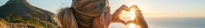Ung kvinne ved sjøen som ser på solnedgang og lager en hjerteformet fingerramme. Skutt i Cape Town, Sør-Afrika.