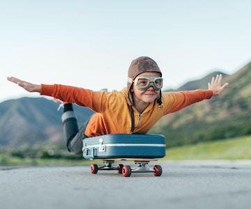 En ung gutt iført flybriller og flyhette har pakket kofferten og lagt den på et skateboard. Han er klar til å fly bort med armene utstrakt til drømmemålet. Bildet er tatt i Utah, USA.