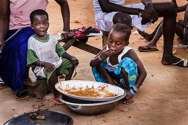 """To senegaleske barn som spiser ris i en landsby  i Senegal."