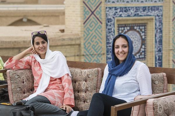 Ung, kvinnelig, vestlig turist og hennes kvinnelige iranske turguide sitter i en typisk takkafé i byen Yazd, Iran. Begge har på seg det typiske enkle hodeskjerfet (hijab eller rousari).