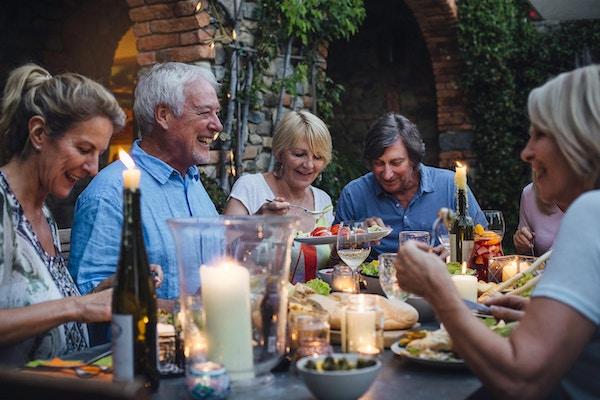 En gruppe voksne venner sitter rundt et utendørs spisebord, spiser og drikker.