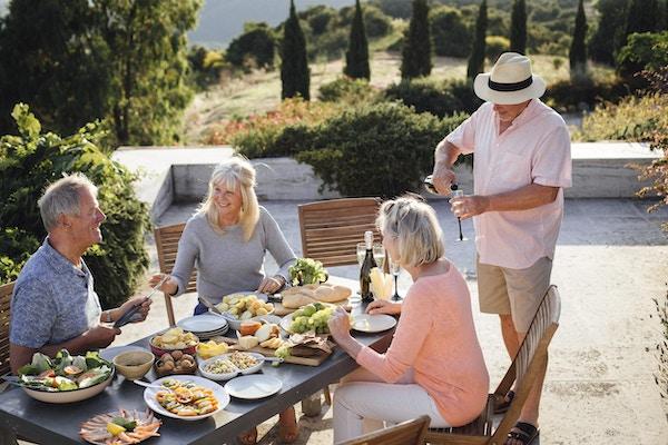En gruppe voksne venner sitter rundt et utendørs spisebord, spiser og drikker. De feirer ferien med et glass champagne og koser seg med hverandres selskap. Bildet er tatt i Toscana, Italia.