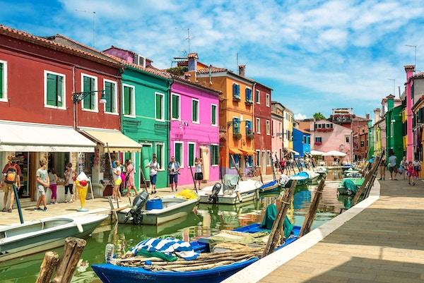 Fargerike hus på øya Burano i Venezia. Båter i kanalen.