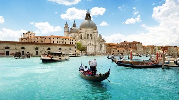 Utsikt over kanalen i Venezia. Gondoler og ferger frakter passasjerer.