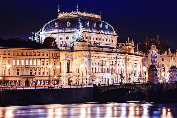 Nattutsikt over Nationaltheatret ved bredden av elven Vltava i Praha.