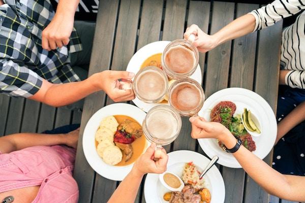 Fire venner som skåler med ølglass på en kafé.