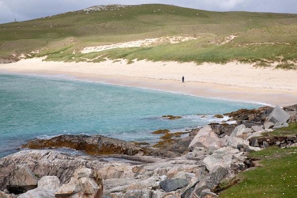Mann på hvit sandstrand i Skottland.