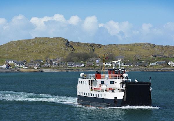 En ferge går tilbake fra Isle of Iona til Isle of Mull i Skottland over nydelig blått farvann.