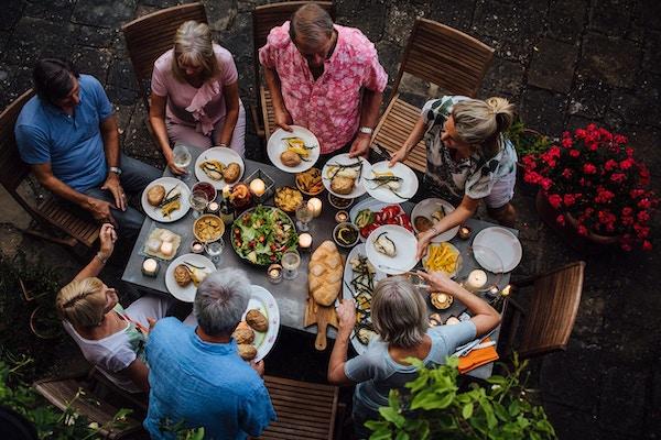 Mennesker sitter rundt et bord og spiser, Italia.