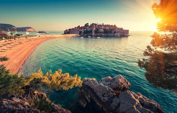Vakkert landskap av feriestedet og stranden i Sveti Stefan i solnedgangen. Montenegro. Adriaterhavet.