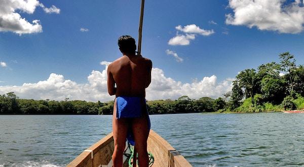 Sentralamerikanske guide som fører båten. Elv, blå himmel, skyer og grønn skog.