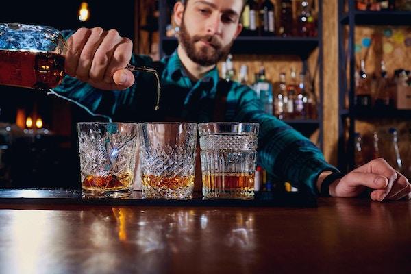 Barmannen skjenker alkohol i et glass. Nærbilde.