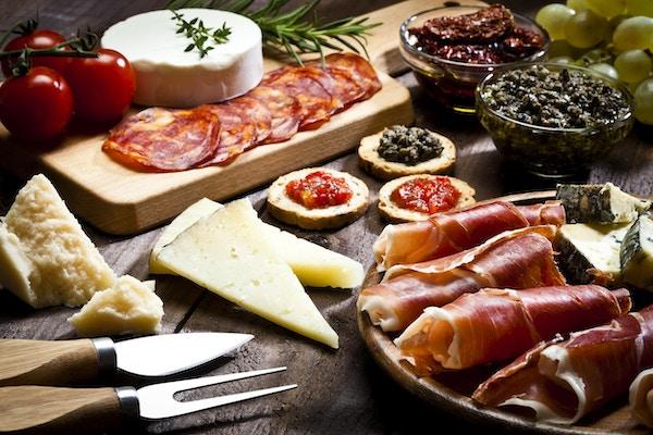 Rustikk trebord fylt med et utvalg av god mat. Et trebrett med prosciutto og ost er nederst til høyre på rammen. To glassboller med tørkede tomater og olivenpasta og et skjærebrett er øverst.